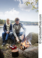 Couple Preparing Bonfire During Lakeside Camping - Young...