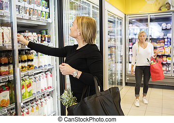 Woman Choosing Juice Packets In Grocery Store - Beautiful...