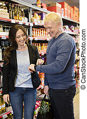 Happy Couple Using Smart Watch In Grocery Store - Happy...