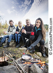 Woman Cooking Food On Campfire With Friends At Lakeshore -...