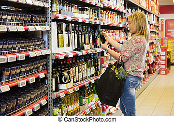 Woman Holding Olive Oil Bottle In Supermarket - Side view of...