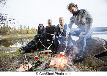 Friends Roasting Marshmallows Over Campfire On Lakeshore -...