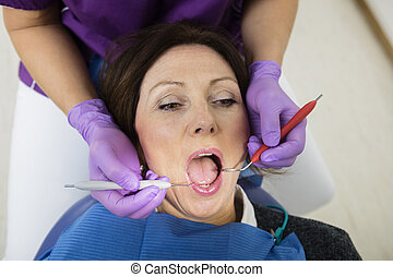 Patient With Mouth Open Being Examined By Dentist Holding...