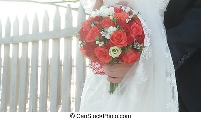 Festive bouquet of red roses in hands of bride