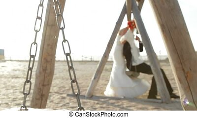 Newlyweds On A Swing - Bride and groom on a swing