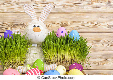 Toy little Easter bunny and Easter eggs on green grass. Easter concept.