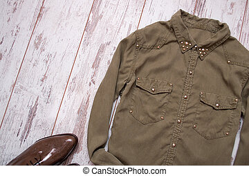 Khaki-colored shirt with rivets, lacquered shoes. Wooden background, space for text. Fashion concept. top view