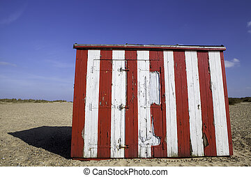 Budget vacation property. Striped beach hut. - A red and...