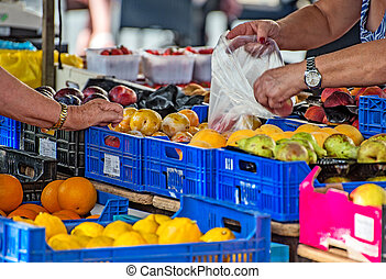 Elderly woman buying fruits on the market.