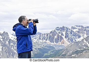 Photographer in mountains - Male photographer taking...
