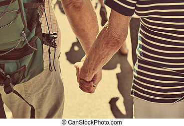 Elderly couple of tourists holding hands.