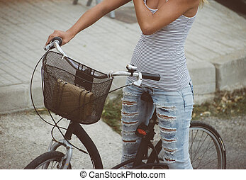 Young girl with old bicycle in the city.