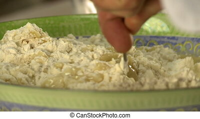 Cooking dough. View of chef add water to flour, close-up
