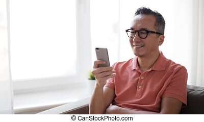 happy man having video call on smartphone at home -...