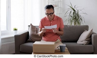 man reading invoice and opening box at home - delivery,...