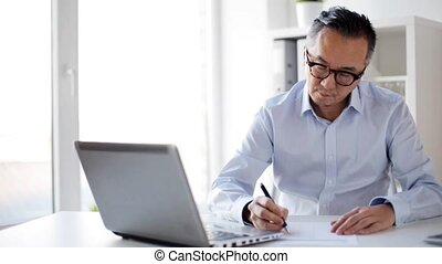 businessman with laptop and papers at office - business,...