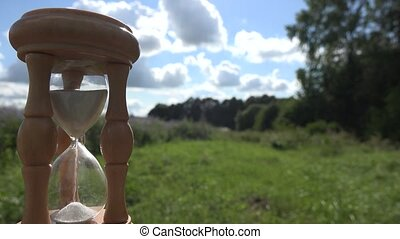 Time measure with wooden sandglass on fields and sky background.