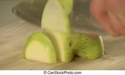 Cooker cutting fresh green apple on cookery board - Cooker...