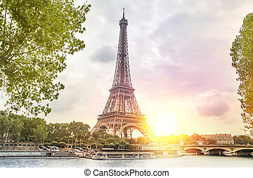 Romantic sunset background. Eiffel Tower with boats on Seine...