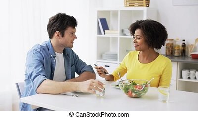 happy couple eating vegetable salad at home - food, people...