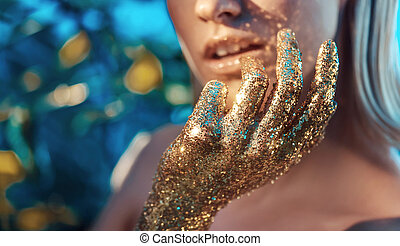 Conceptual portrait of the woman with golden hands