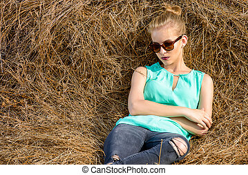 girl lying on a haystack - Blonde fashionable woman on a...