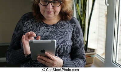 Attractive mature woman with computer tablet browsing the internet at home