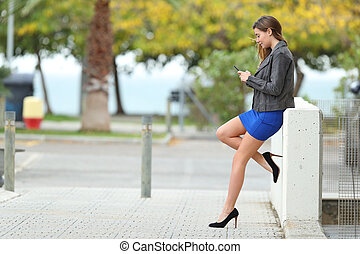 Fashion girl with long perfect legs using phone - Side view...