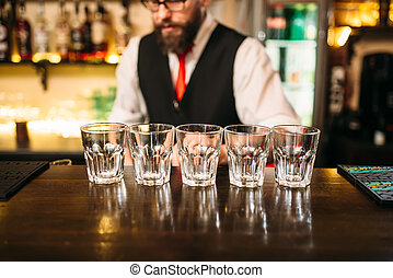 Empty glasses on wooden bar counter, bartender working on...