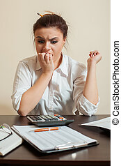Frightened accountant looks at the balance sheet -...