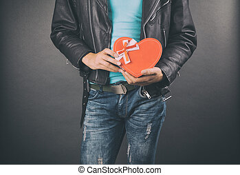 happy young man holding gift box  over gray background