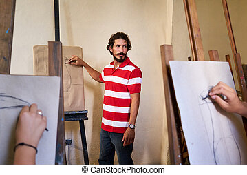 Man At Work As Teacher In Art School With Students - School...