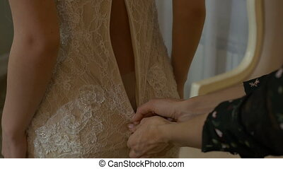 Stylist helps the bride to wear a dress - Stylist helps the...
