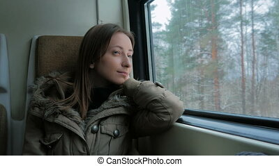 Pensive woman relaxing and looking out of a train window....