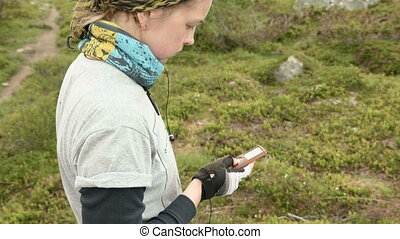 Girl selects music on media player outdoors