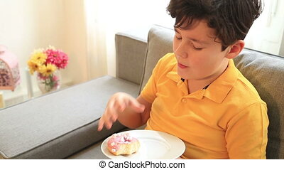 Child eating donut - Young boy eating sweet donuts at home