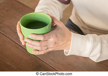 Woman hand on hot green tea drinking, stock photo