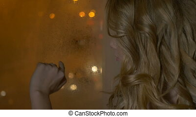 Beautiful girl thoughtfully looking out the window -...