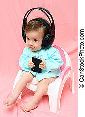 baby in headphones on chamber-pot - baby in headphones with...