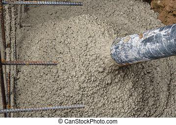 Pouring concrete - Concrete pumping hose filling foundation...