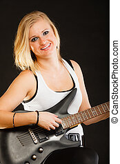 Woman playing on electric guitar, black background - Music,...