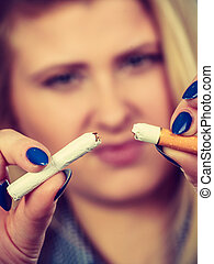 Woman breaking cigarette, getting rid of addiction
