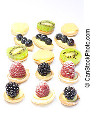 Miniature pastries with fresh berries and fruits