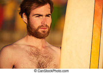 Rugged bearded male surfer portrait next to surf board -...