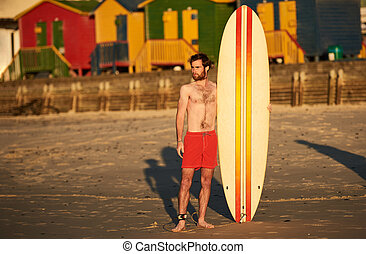 Colourful image of male surfer on beach with surfboard -...