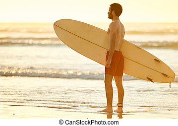 Profile of man holding a surfboard on the beach - Young...