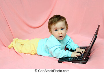 baby lying with laptop