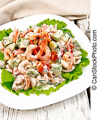 Salad with shrimp and tomato on lettuce in plate