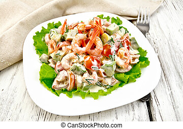 Salad with shrimp and avocado in white plate on light board