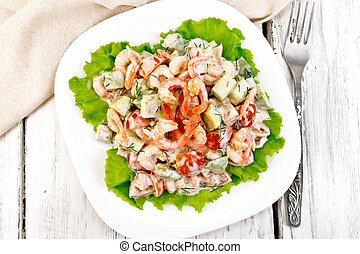 Salad with shrimp and avocado in plate on board top
